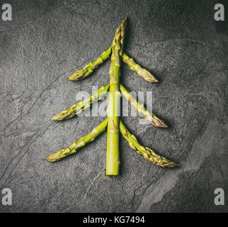 Christmas Food background. Christmas tree made from fresh asparagus on black stone slate background. Healthy holiday - Stock Photo
