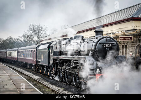 A steam locomotive pulls into the platform at Ramsbottom Station on The East Lancs Railway - Stock Photo