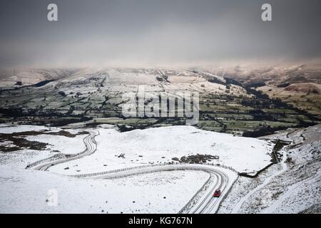 A car drives up a snow covered mountain road in winter. Edale valley, Peak District, UK - Stock Photo