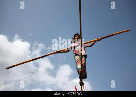 A street trapeze artist performs the balancing act on a tight rope in India. - Stock Photo