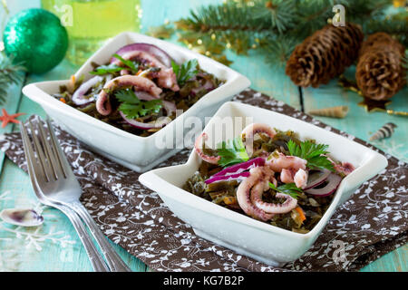 Home snack on a gray stone or slate background. Salad with octopus and sea cabbage. The concept of healthy eating. - Stock Photo