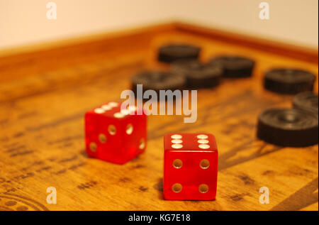 The old oriental game - backgammon, two red dice, black chips - Stock Photo