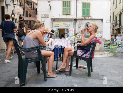 Women enjoying food at pavement cafe, San Remo, Italy. - Stock Photo