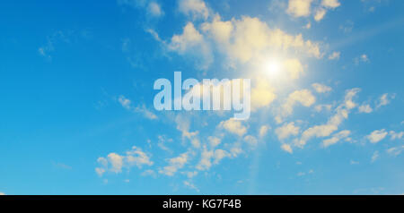 Bright sun on a background of blue sky and clouds. - Stock Photo