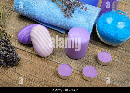 Goods for the spa: soap, sea salt, towel, oil of lavender on a wooden background. - Stock Photo