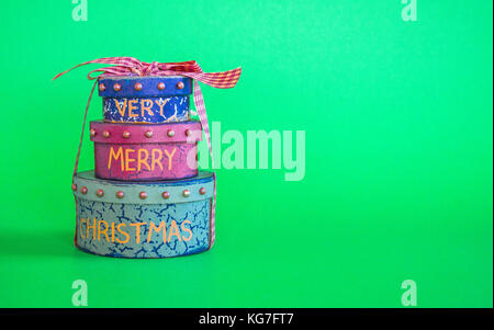 stack of 3 Christmas gift boxes tied with ribbon isolated on green background - Stock Photo