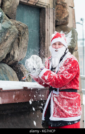 STOCKHOLM, SWEDEN – DECEMBER 11, 2016: Young man dressed up as santa preparing to throw a snowball, during charity - Stock Photo