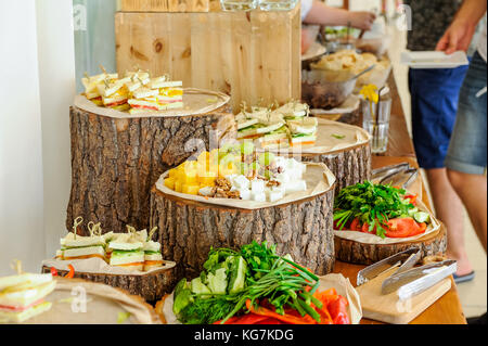 Outside Catering buffet table with a delicious food for guests of the event in rustic style. Service at business - Stock Photo