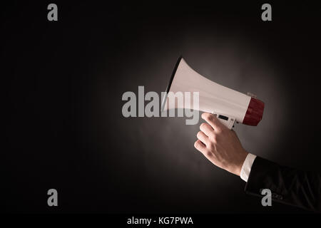 Hand of a businessman holding a megaphone - Stock Photo