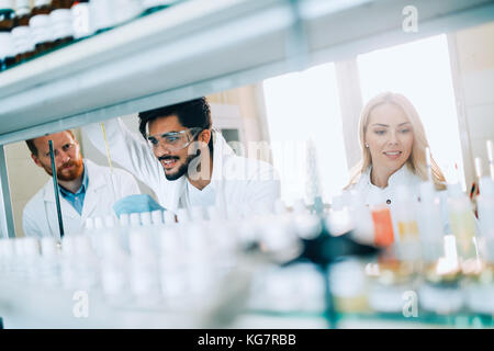 Group of chemistry students working in laboratory - Stock Photo