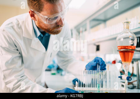 Handsome student of chemistry working in laboratory - Stock Photo