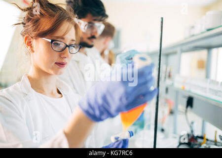 Young students of chemistry working in laboratory - Stock Photo