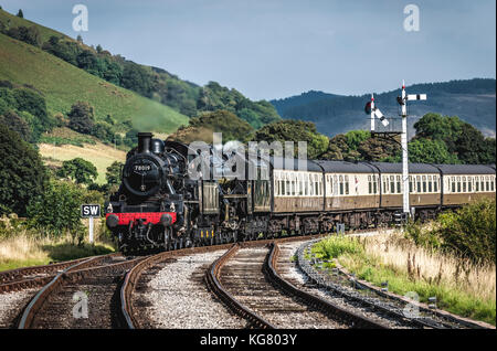 A steam locomotive rounds a bend as it approaches Corwen Station on the Llangollen Railway in North Wales - Stock Photo
