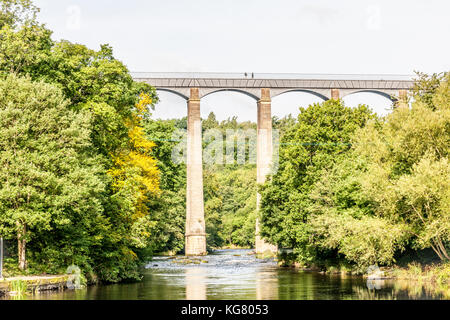 Two people walk along the Pontcysyllte Aqueduct as it carries the Llangollen Canal over the River Dee in Llangollen, - Stock Photo