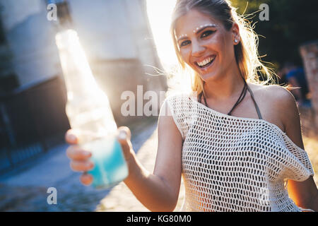 Portrait of happy young girl holding drink - Stock Photo