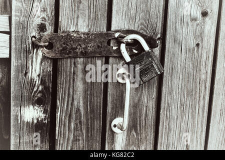 Old rusty padlock on a decaying fence. Security concept: open padlock on wooden wall. Black and white colors. - Stock Photo