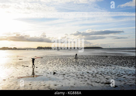 Poole, UK. 4th November, 2017. A pair of windsurfers make their way to shore as the sun begins to set over Poole - Stock Photo