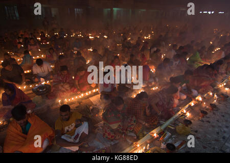 Dhaka, Bangladesh. 4th November 2017. Devotees attend prayer with burning incense and light oil lamps before break - Stock Photo