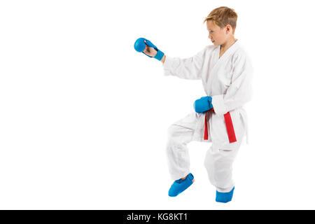 Pre-teen boy doing karate on a white background - Stock Photo