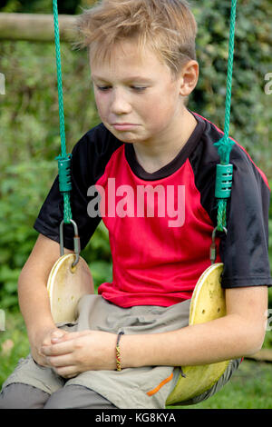 Sad pre-teen boy sitting on a swing outside - Stock Photo