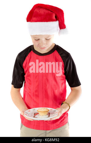 Pre-teen boy in christmas hat and a mince pie - Stock Photo