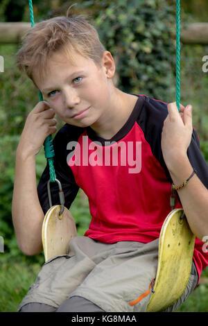 Sad pre-teen boy sitting on a swing outside - Stock Photo