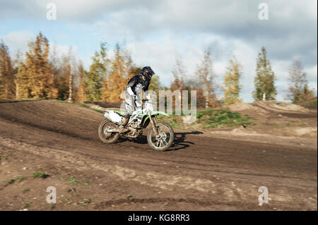 Motocross driver in action landing the motorbike after the jump on the race track - Stock Photo