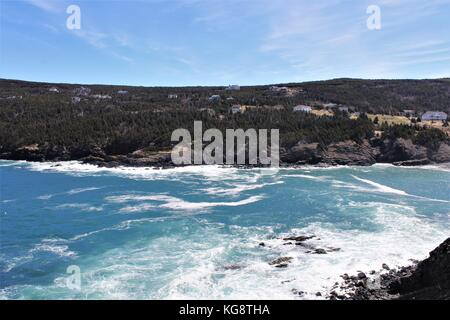 Waves breaking against the rocky cliffs and rugged coastline, Logy Bay-Middle Cove-Outer Cove, Newfoundland Labrador - Stock Photo