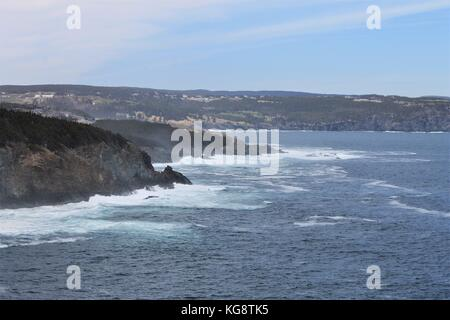 Waves breaking against the cliffs, Logy Bay-Middle Cove-Outer Cove, Newfoundland and Labrador, Canada. Light fog, - Stock Photo