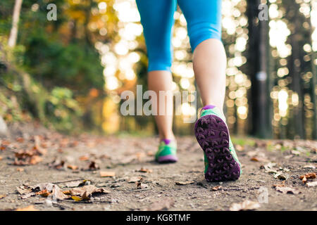 Woman walking and hiking in autumn forest, sport shoes. Jogging, trekking or training outside in autumn nature. - Stock Photo