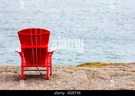 A red Adirondack chair anchored to the cliff, facing out toward the sea, trail side, Signal Hill, St. John's, Newfoundland - Stock Photo