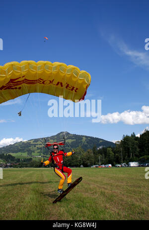 Canopy Swooping Skydiver Under Is Suring His Sky Board During A Parachute Landing