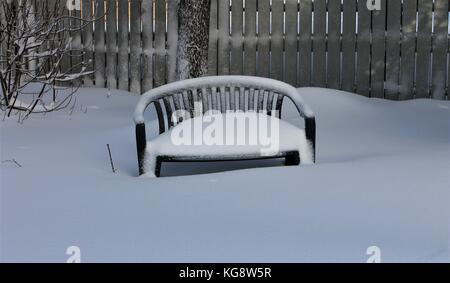 Garden bench covered in snow after spring snowfall - Stock Photo