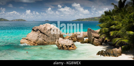 The Seychelles, La Digue, Anse Patates, tourist in sea sheltered behind huge granite rocks - Stock Photo