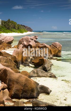 The Seychelles, La Digue, Anse Formis, east coast, rocky shore, beach and shallow lagoon - Stock Photo