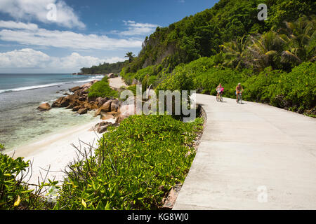 The Seychelles, La Digue, Anse Formis, two older tourists cycling on empty east coast road - Stock Photo