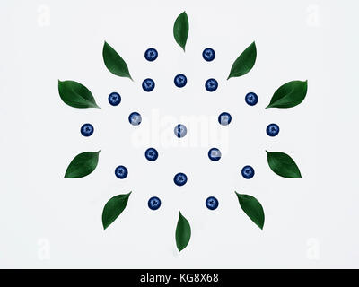 Blueberries and leaves isolated Bright green leaves and blueberries are lying on a white background Flat lay Modern - Stock Photo