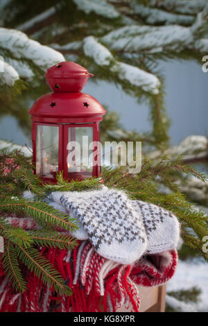 Scandinavian style wool mittens on the Christmas plaid near red lantern. Toned.