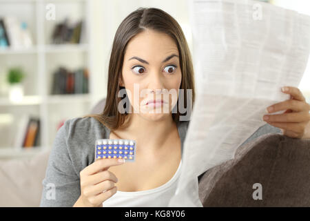 Portrait of a confused girl reading contraindications in a leaflet of contraceptive pills sitting on a couch in - Stock Photo