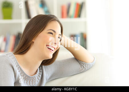 Portrait of a happy pensive girl looking away sitting on a sofa in the living room at home with copy space in white - Stock Photo
