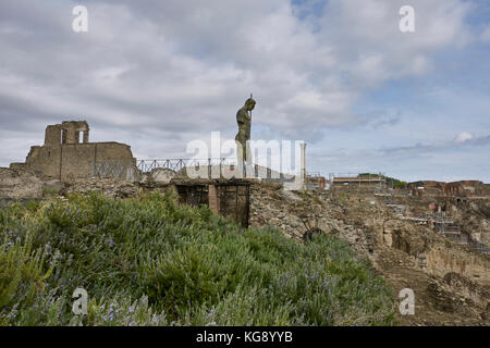 Pompeii ruins exhibited after archaeological excavations. Modern sculpture by the sculptor Igor Mitoraj adjacent - Stock Photo