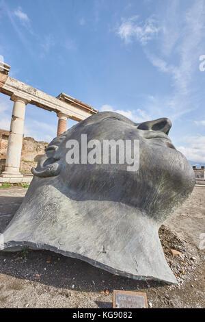 Pompeii ruins exhibited after archaeological excavations. Sculptor Igor Mitoraj's bronze head 'Memorie' - Stock Photo