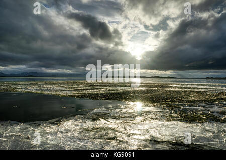 Winter Landscape frozen lake with ice floes and cloudy sky in Ic - Stock Photo