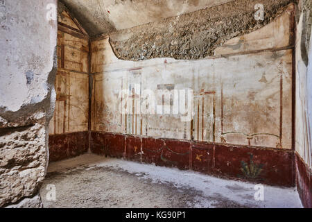 Pompeii ruins exhibited after archaeological excavations. Decorated walls in room. - Stock Photo