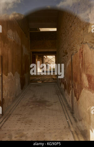 Pompeii ruins exhibited after archaeological excavations. Passageway with decorated  floor and walls. - Stock Photo