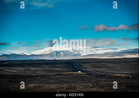 View across black beach towards eyjafjallajokull volcano - Stock Photo