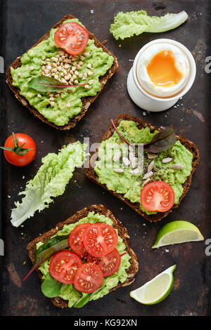 Healthy green veggie toast with avocado, tomato, sprouts and seeds and boiled egg on rusty background. Table top - Stock Photo