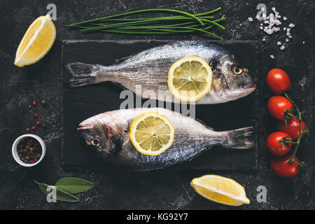 Fresh sea beam or dorado fish, lemon, herbs, spices and vegetables on black stone slate background. Top view. Fresh - Stock Photo