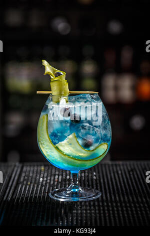 Blue gin tonic with cucumber served on the bar counter - Stock Photo