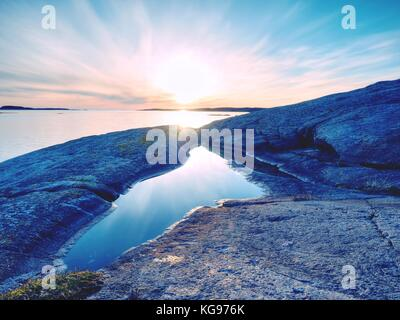 Beautiful seascape view. The mirroring of  sunsetting horizon in water pools in the rocks . Smooth ocean with light - Stock Photo